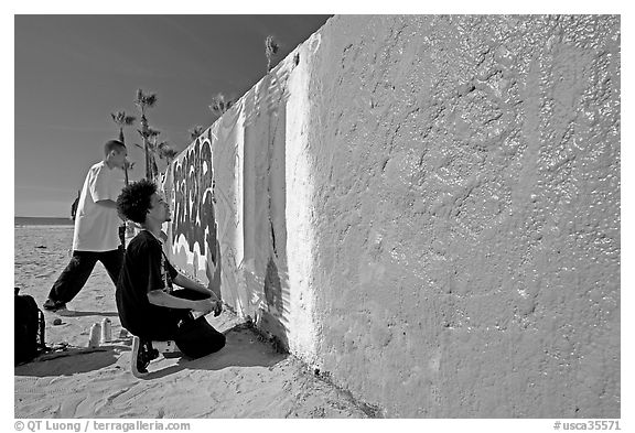 Young men creating graffiti art on a wall on the beach. Venice, Los Angeles, California, USA (black and white)