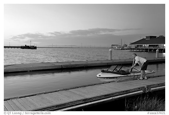 Man holding small boat, Redwood marina, sunset. Redwood City,  California, USA (black and white)