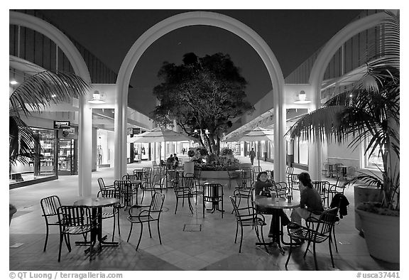 Sitting at outdoor table at night, Stanford Shopping Center. Stanford University, California, USA (black and white)