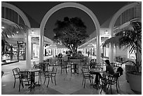 Sitting at outdoor table at night, Stanford Shopping Center. Stanford University, California, USA ( black and white)
