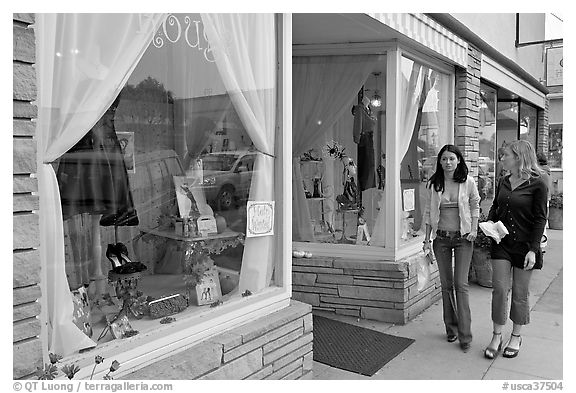 Women walking by storefront on Main Street. Half Moon Bay, California, USA (black and white)