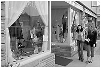 Women walking by storefront on Main Street. Half Moon Bay, California, USA ( black and white)