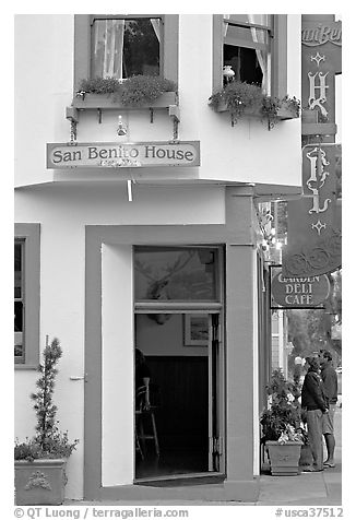 Entrance of historic San Benito House, with couple looking. Half Moon Bay, California, USA