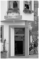 Entrance of historic San Benito House, with couple looking. Half Moon Bay, California, USA (black and white)