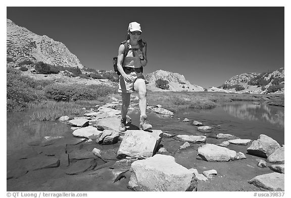 Woman crossing stream on rocks, John Muir Wilderness. California, USA (black and white)