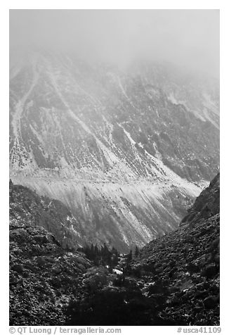 Mountains cut by Tioga Pass road with fresh snow. California, USA (black and white)