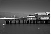 Man on buoy and pier. Santa Barbara, California, USA (black and white)