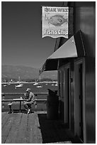 Man eating on wharf next to Fish and Chips restaurant. Santa Barbara, California, USA (black and white)
