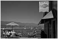 People eating with yachts and beach in background. Santa Barbara, California, USA (black and white)