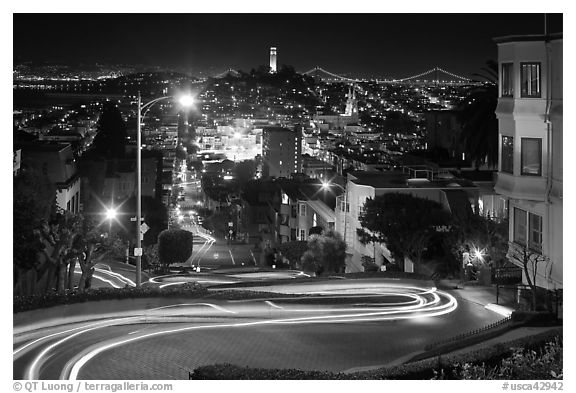 Sharp switchbacks on Russian Hill with Telegraph Hill in the background, night. San Francisco, California, USA (black and white)