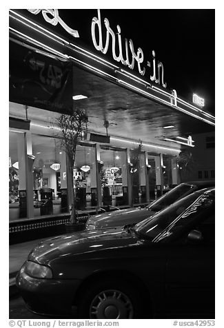 Neon lights of Mels drive-in reflected on parked cars. San Francisco, California, USA
