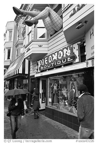 Woman passing with unbrella below giant legs. San Francisco, California, USA (black and white)