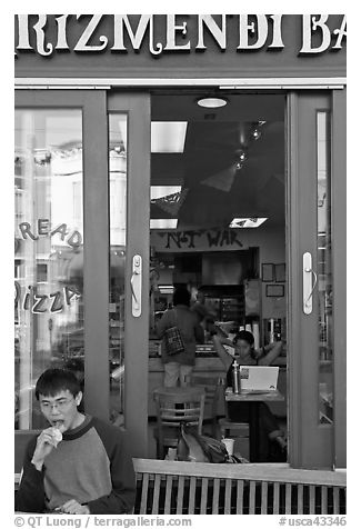 Man biting pizza outside pizzaria, Haight-Ashbury district. San Francisco, California, USA (black and white)