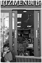 Man biting pizza outside pizzaria, Haight-Ashbury district. San Francisco, California, USA ( black and white)