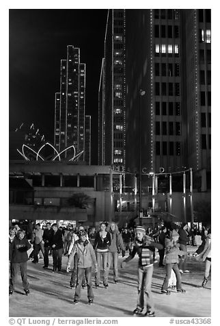 People skating on ice ring at night, Embarcadero Center. San Francisco, California, USA (black and white)