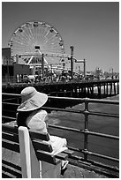 Woman sitting on bench with pink hat and ferris wheel. Santa Monica, Los Angeles, California, USA ( black and white)