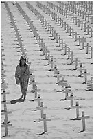 Girl wrapped in towel walking amongst crosses on beach. Santa Monica, Los Angeles, California, USA (black and white)