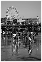 Pier and beachgoers reflected in wet sand, late afternoon. Santa Monica, Los Angeles, California, USA ( black and white)