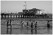 People bathing in ocean and Santa Monica Pier, late afternoon. Santa Monica, Los Angeles, California, USA (black and white)