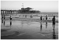 Beachgoers near Santa Monica Pier reflected in wet sand, sunset. Santa Monica, Los Angeles, California, USA (black and white)
