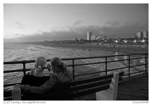 Two women sitting on bench at sunset , Santa Monica Pier. Santa Monica, Los Angeles, California, USA