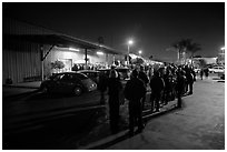 People lining up to enter a gallery at night, Bergamot Station. Santa Monica, Los Angeles, California, USA (black and white)