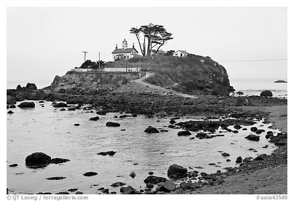 Rocky mound and lighthouse, Crescent City. California, USA (black and white)