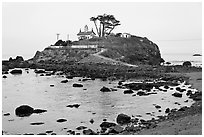 Rocky mound and lighthouse, Crescent City. California, USA ( black and white)