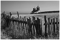 Fences, summer grass and chapel towers, Fort Ross. Sonoma Coast, California, USA (black and white)