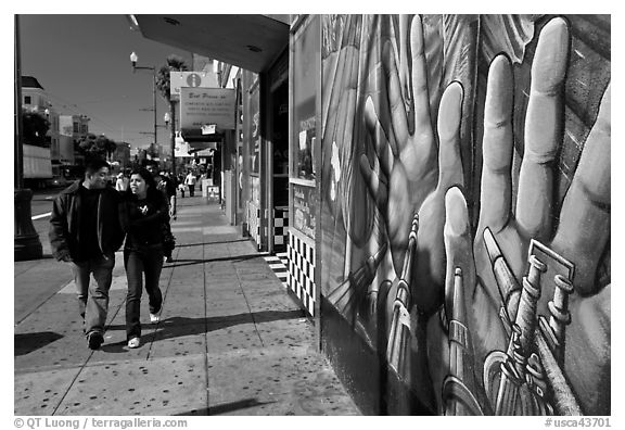 Couple walks past mural on Mission street, Mission District. San Francisco, California, USA (black and white)