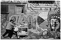 Man pushes vending cart pass mural and bicycle, Mission District. San Francisco, California, USA (black and white)