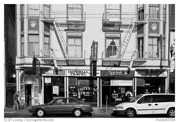 Buildings, cars, and sidewalk, Mission Street, Mission District. San Francisco, California, USA (black and white)