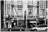 Buildings, cars, and sidewalk, Mission Street, Mission District. San Francisco, California, USA ( black and white)