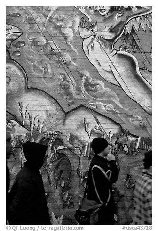 Men in dark jackets walk past mural, Mission District. San Francisco, California, USA (black and white)