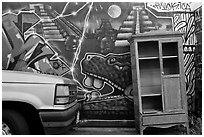 Car, mural, and discarded furniture, Mission District. San Francisco, California, USA (black and white)