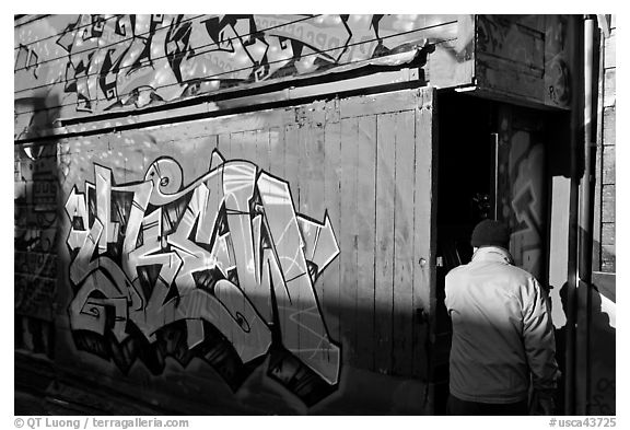 Man opening door of painted garage, Mission District. San Francisco, California, USA (black and white)