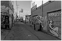 Alley (Lilac) with many murals and decorated garage doors, Mission District. San Francisco, California, USA (black and white)