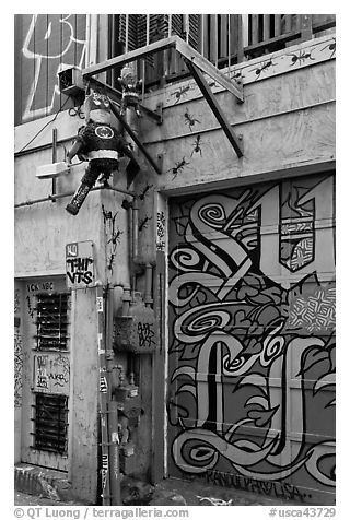 Painted garage door and suspended pinata figures, Mission District. San Francisco, California, USA (black and white)