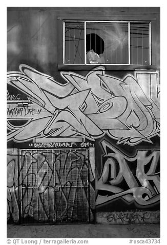 Mural paintings below broken window, Mission District. San Francisco, California, USA (black and white)