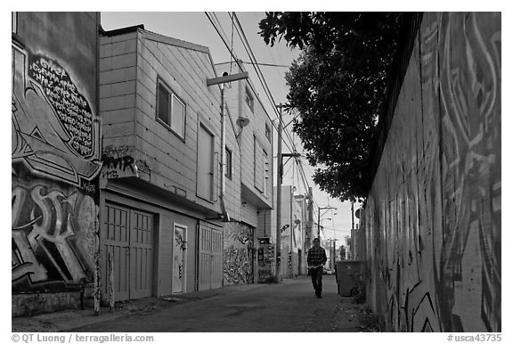 Man walking in alley, Mission District. San Francisco, California, USA (black and white)