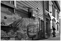 Mural and man entering house with grocery bags, Mission District. San Francisco, California, USA ( black and white)