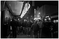 Men walking on sidewalk, Castro street at night. San Francisco, California, USA ( black and white)