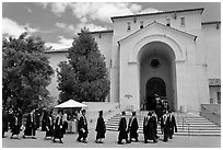 Graduates walking single file into Memorial auditorium. Stanford University, California, USA (black and white)