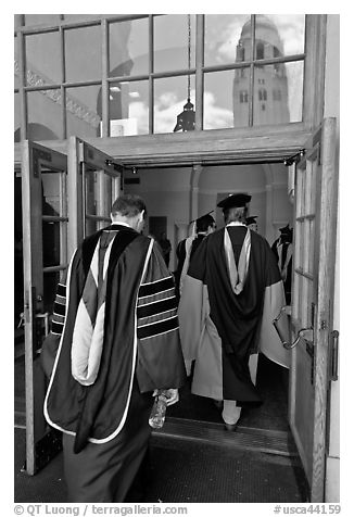 Professors in academic regalia walk into door with Hoover tower reflected. Stanford University, California, USA (black and white)