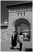 Graduate and family member walking through Main Quad. Stanford University, California, USA (black and white)
