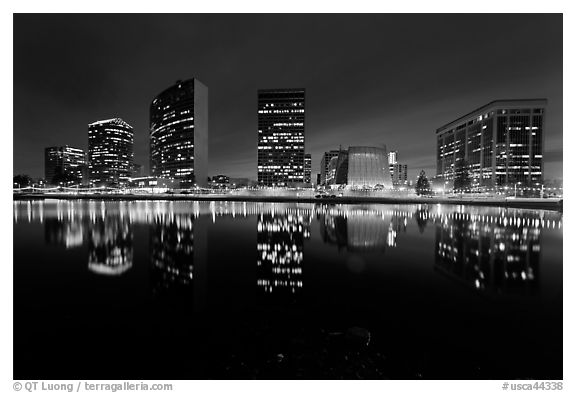High-rise buildings and Oakland Cathedral reflected in Lake Meritt at night. Oakland, California, USA (black and white)