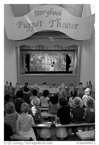 Children look at Snow white puppet show, Fairyland. Oakland, California, USA (black and white)