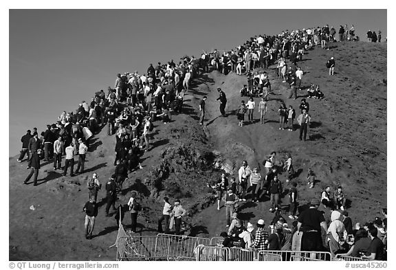 Crowds scrambling on hill during mavericks competition. Half Moon Bay, California, USA (black and white)