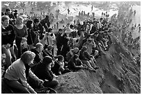 Spectators sitting on cliff to see mavericks contest. Half Moon Bay, California, USA (black and white)