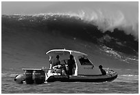 Small boat dwarfed by huge wave. Half Moon Bay, California, USA ( black and white)